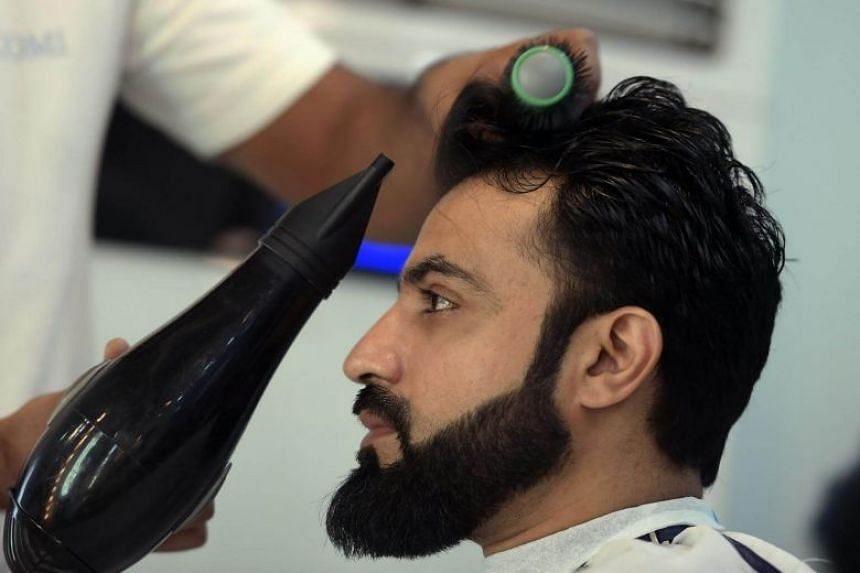 A male hairdresser blow-drying a customer's hair at a men's salon in Islamabad, on Oct 10, 2017.