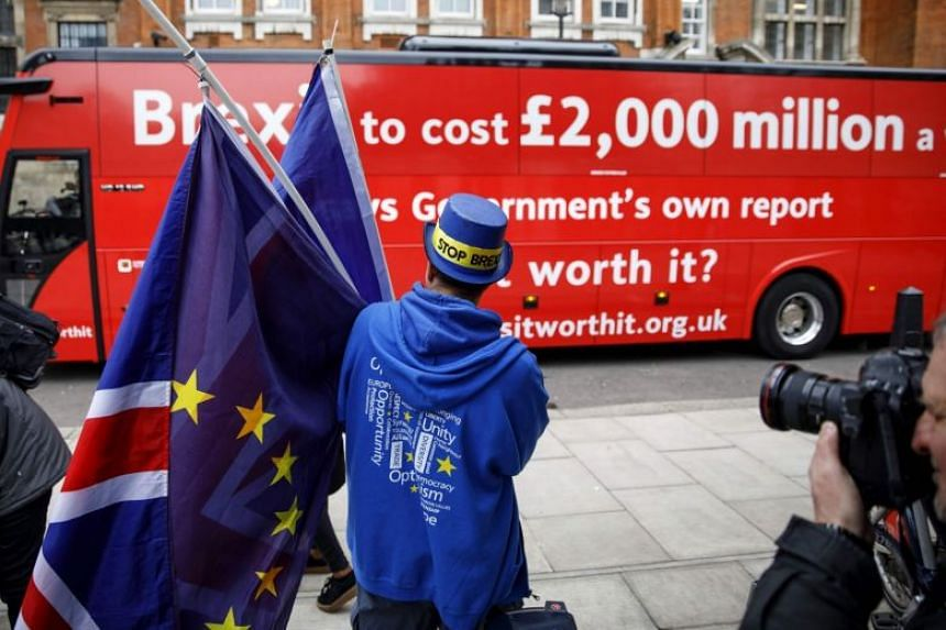 A pro-European Union campaigner watches as the Brexit Facts Bus, rolled out by EU advocates as they kick off a new initiative against Brexit, leaves College Green in London on Feb 21, 2018.