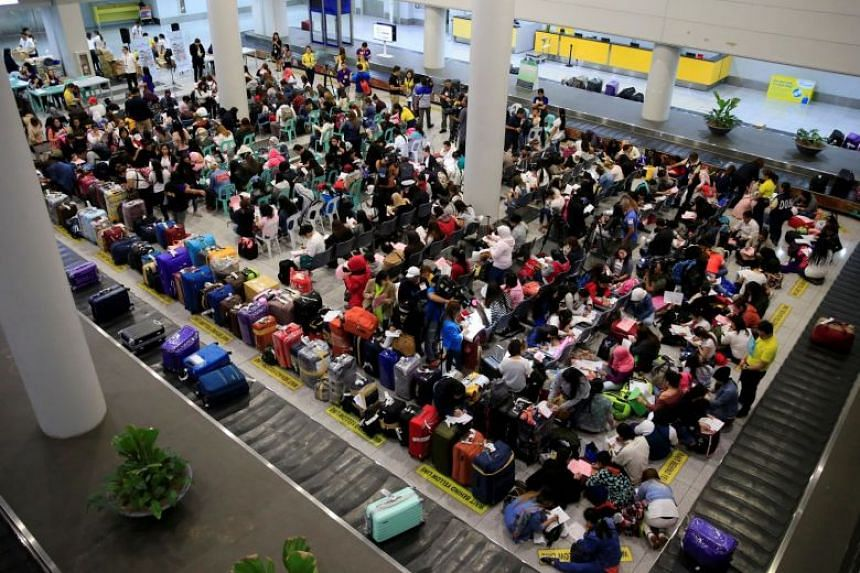 Overseas Filipino workers from Kuwait gathering after their arrival at the Ninoy Aquino International Airport in Pasay city, Metro Manila, on Feb 21, 2018.