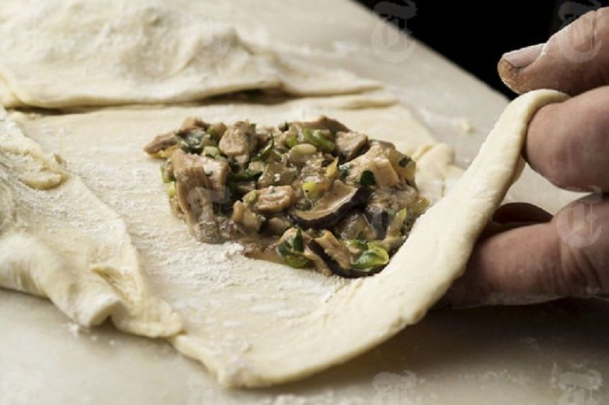 Chicken and mushroom filling on puff pastry dough.