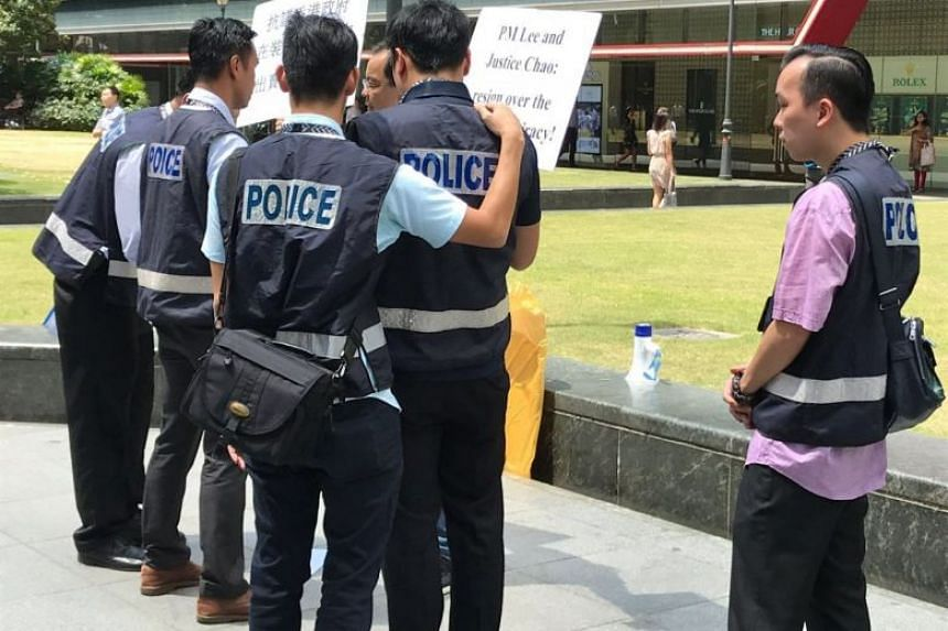 A 41-year-old man was arrested for holding placards outside Raffles Place MRT at around 12pm on Feb 22, 2018.