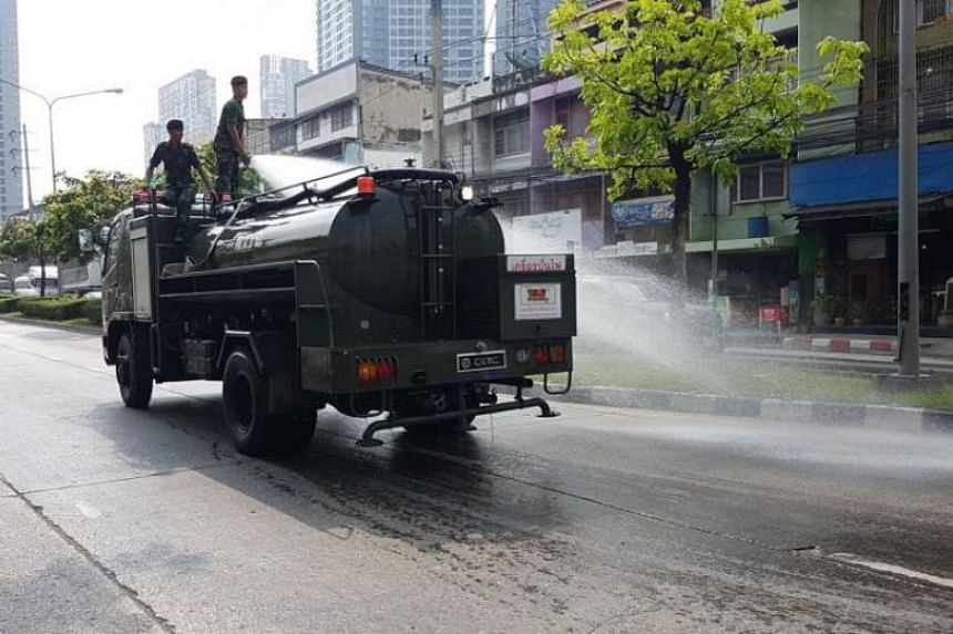 Members of Thailand's army clean up dirt brought about by the recent air pollution in Bangkok on Feb 18, 2018.