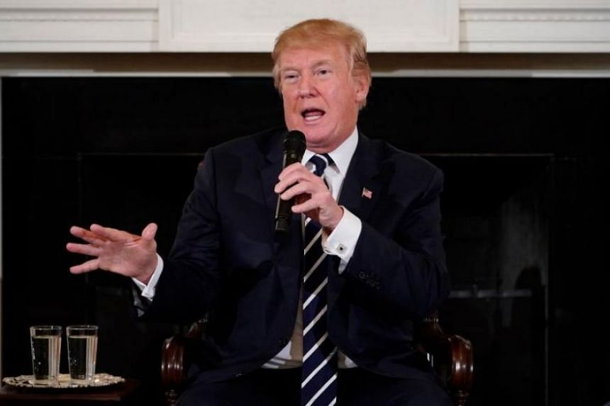 """US President Donald Trump taking part in a """"listening session"""" on gun violence with teachers and students at the White House on Feb 21, 2018."""