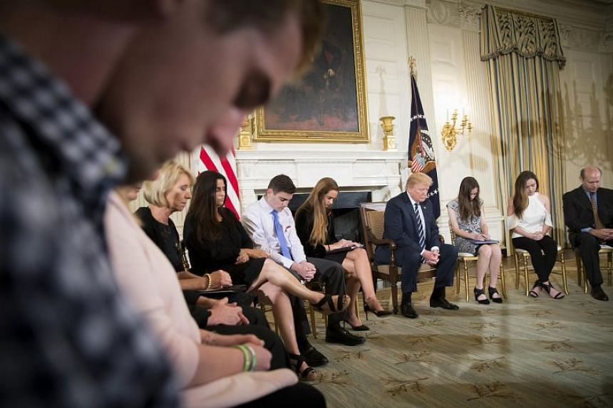 US President Donald Trump bows his head during a prayer before a discussion that included survivors of the Marjory Stoneman Douglas High School mass shooting, in the State Dining Room of the White House on Feb 21, 2018.