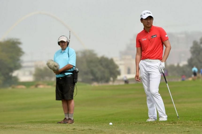 Wang looks on during the first round of the Qatar Masters golf tournament.