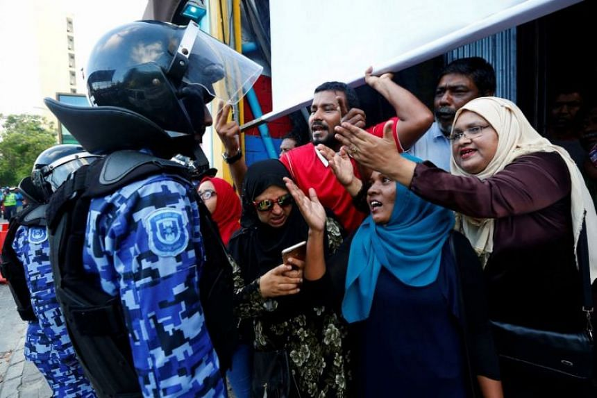 Maldivian opposition supporters arguing with a police officer in Male, Feb 9, 2018.