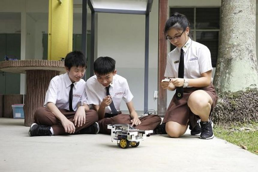 """Bukit View Secondary School students (from left) Marvyn Chia 15, Yeo Swe Hon, 15, and Wong Shi Ya, 16, operating a """"solar car"""". The school's Joules (Junior Outstanding Leaders in Environment for Sustainability) Smart Centre was launched by Environmen"""