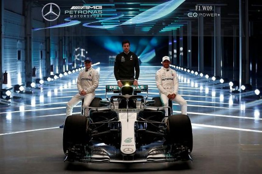 """Mercedes' defending champion Lewis Hamilton (right), Valtteri Bottas and executive director Toto Wolff posing with their new """"diva"""" - the W09 - at Silverstone."""