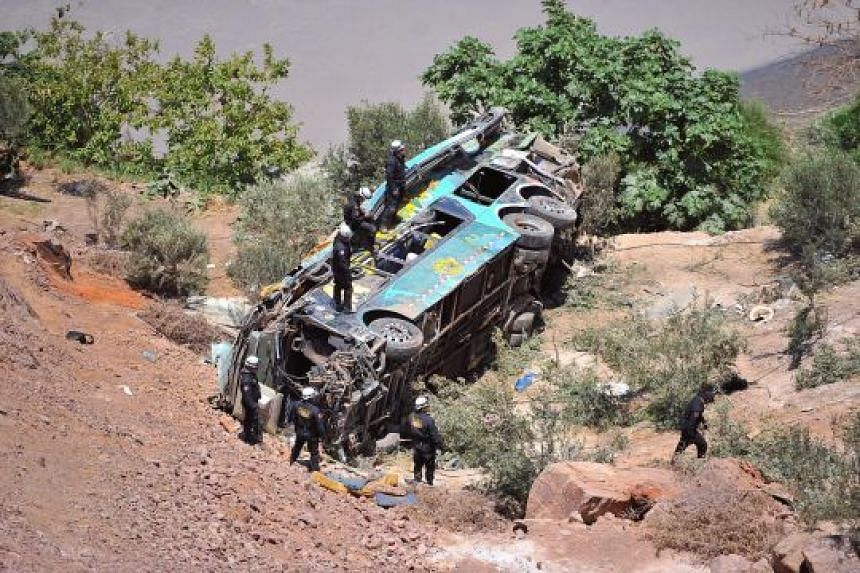 Rescue workers at the scene of the crash site in Arequipa. The double-decker bus had veered off a mountain road and plunged into a ravine.