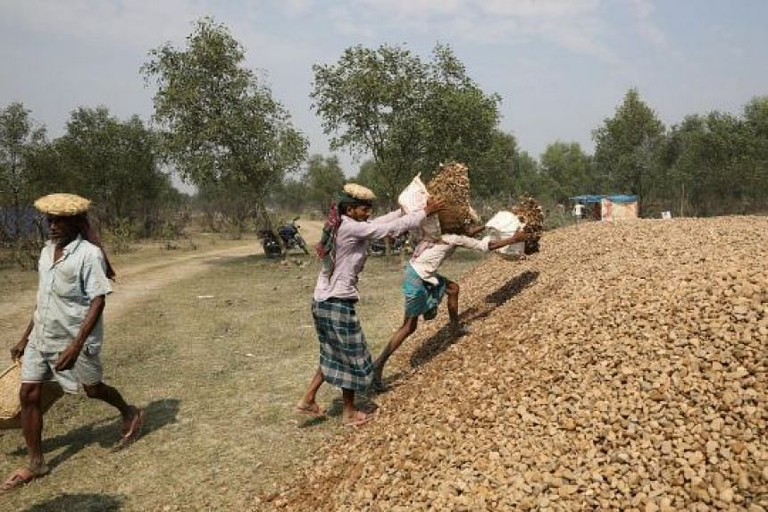Construction workers stack stones on Bhashan Char or Floating Island. Work on the project has accelerated in recent months with satellite images showing roads and what appears to be a helipad on the island.