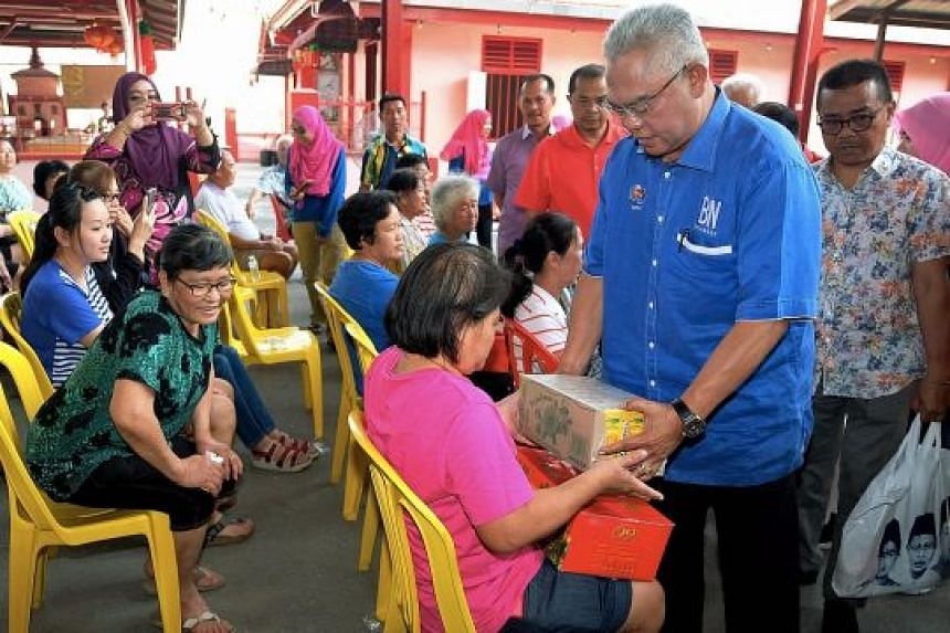 Tan Sri Noh Omar, chairman of Barisan Nasional in Selangor, giving out Chinese New Year goodies to residents in the state last week. The Umno-led ruling coalition is working hard to recapture Malaysia's richest state after 10 years. Umno has recruite