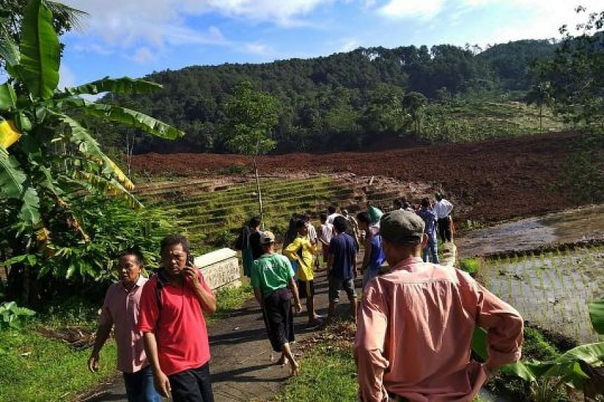 A handout photo from Indonesia's disaster mitigation agency shows residents gathering near the landslide site in Brebes yesterday. The victims were buried under an avalanche of mud and rock.