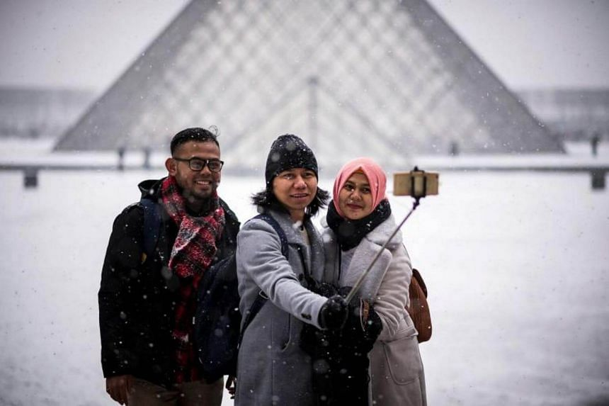 Tourists take a selfie in front of the Louvre Pyramid in Paris on Feb 9, 2018.
