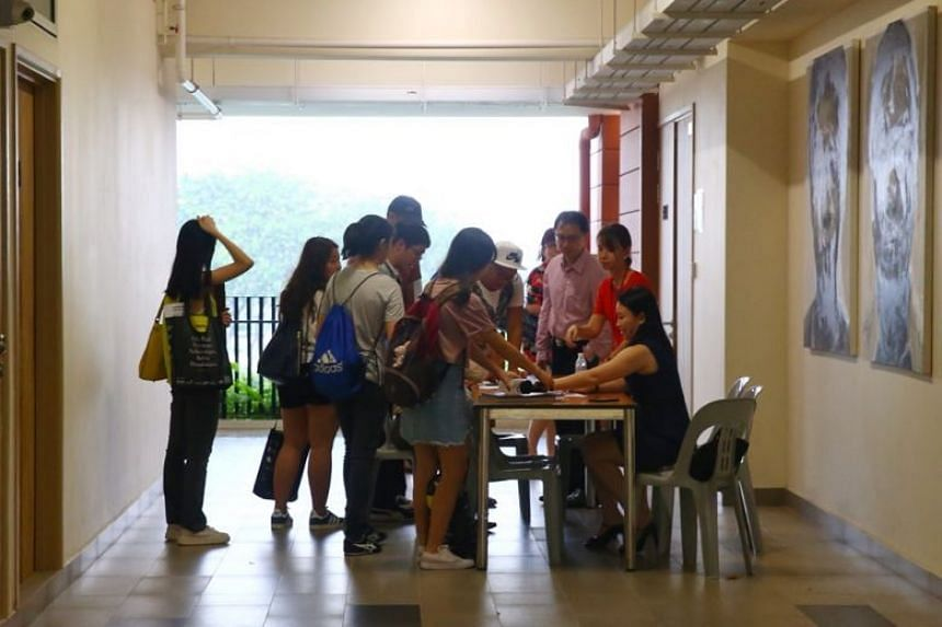 Affected Hwa Chong Institution students check their names against a register before attending a briefing, on Feb 23, 2018.