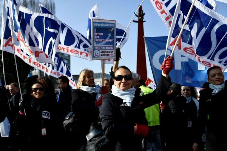 Striking Air France employees hold union flags at Charles de Gaulle airport.