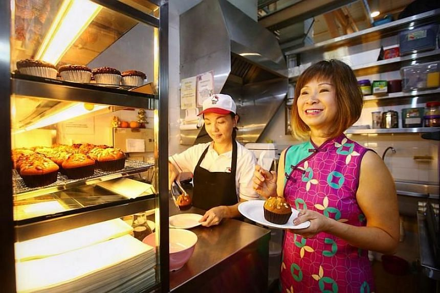 Ms Tan Pey See, 44, who owns a muffin stall at ABC Brickworks Food Centre, with Senior Minister of State for the Environment and Water Resources Dr Amy Khor.