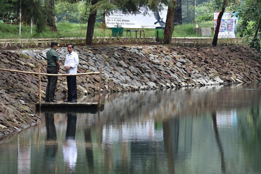 Indonesia President Joko Widodo (right) talk to the local military commander during a visit to Lake Cisanti, the source of the Citarum River, south of Bandung, West Java, Indonesia on Feb 22, 2018.