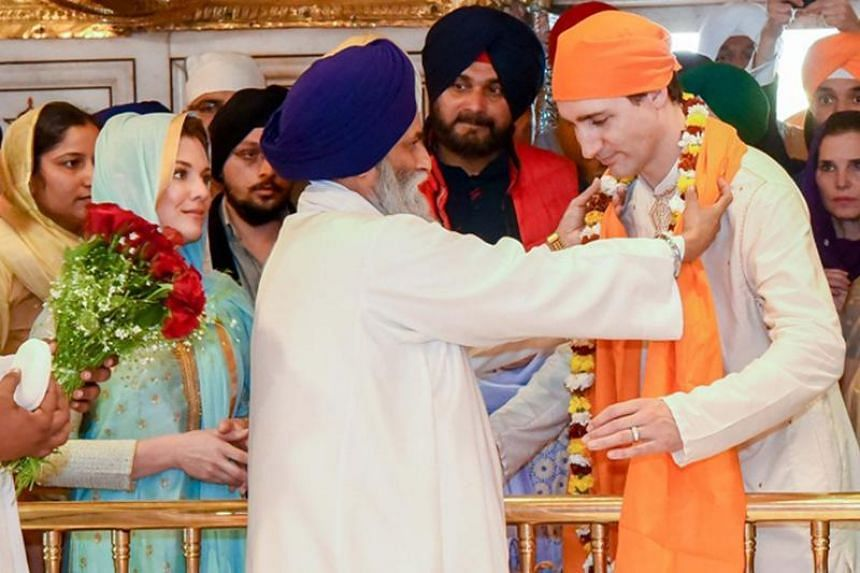 Canadian Prime Minister Justin Trudeau (right) receives a flower garland during a visit to the Golden Temple in Amritsar.