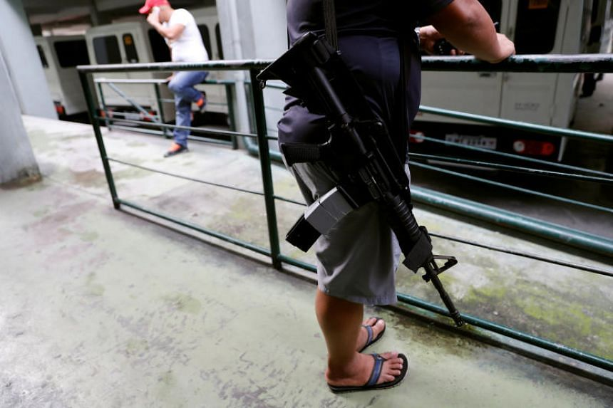 An agent of the Philippine Drugs Enforcement Agency waits for colleagues to conduct a surveillance operation in Quezon city on Dec 10, 2017.