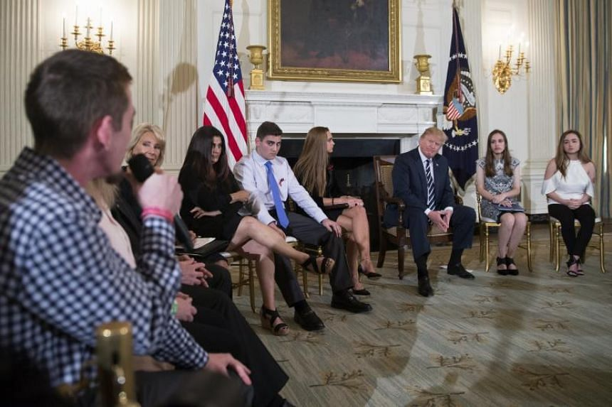Marjory Stoneman Douglas High School shooting survivor Samuel Zeif (left) delivers remarks as US President Donald Trump listens during a listening session with high school students and teachers in the State Dining Room of the White House in Washingto