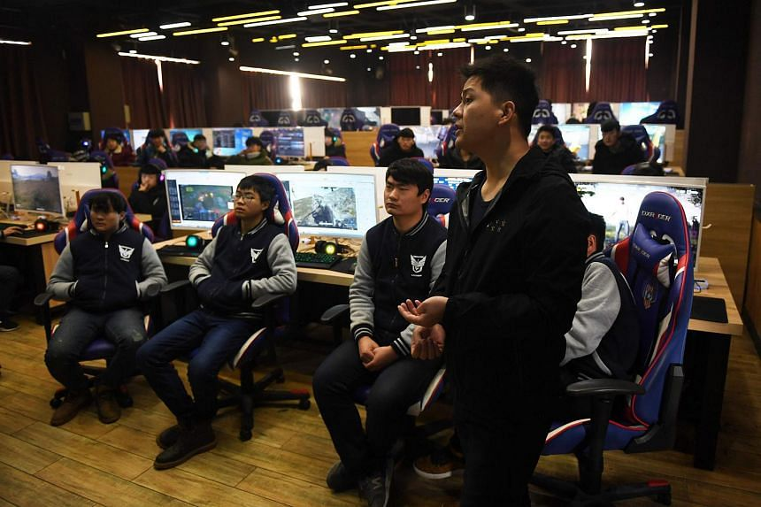 Students listening to teacher Yang Xiao explain game techniques in an eSports class at the Lanxiang technical school in Jinan, in China's eastern Shandong province.