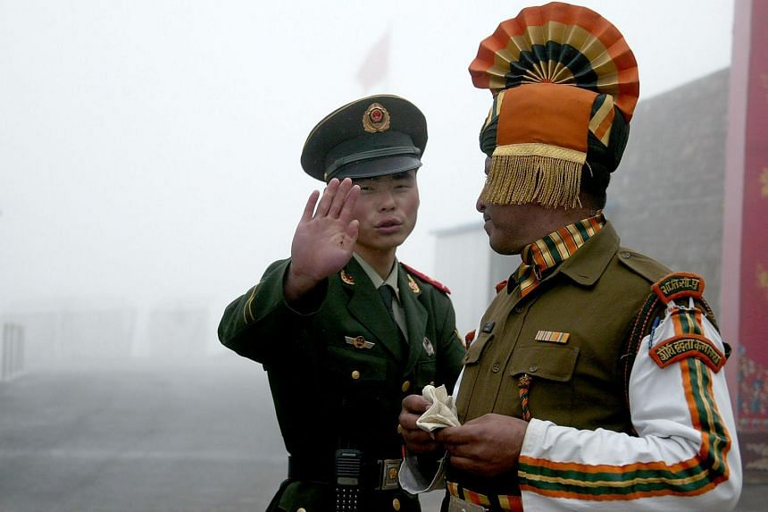 A Chinese soldier (left) gesturing next to an Indian soldier at the Nathu La border crossing between India and China in India's northeastern Sikkim state.