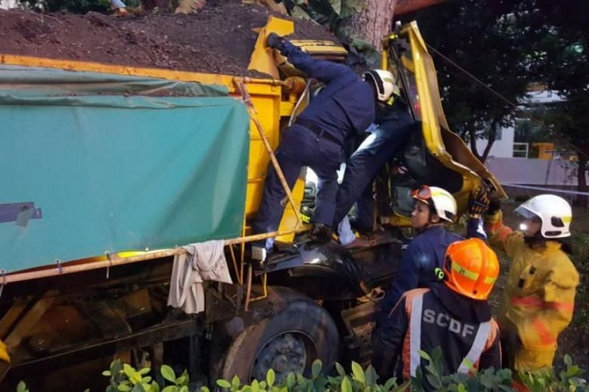 Officers from Singapore Civil Defence Force Disaster Assistance and Rescue Team (Dart) rescue a man in his 30s who was trapped in his seat after his tipper truck crashed into a tree on the East Coast Parkway on Feb 23, 2018.