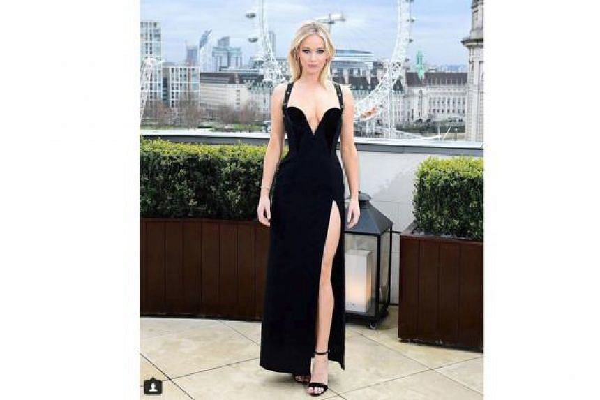 Jennifer Lawrence's black dress (above) brings to mind a similar gown that actress Elizabeth Hurley wore in 1994 (with actor Hugh Grant) - both are by Versace and feature a plunging neckline and a high slit.