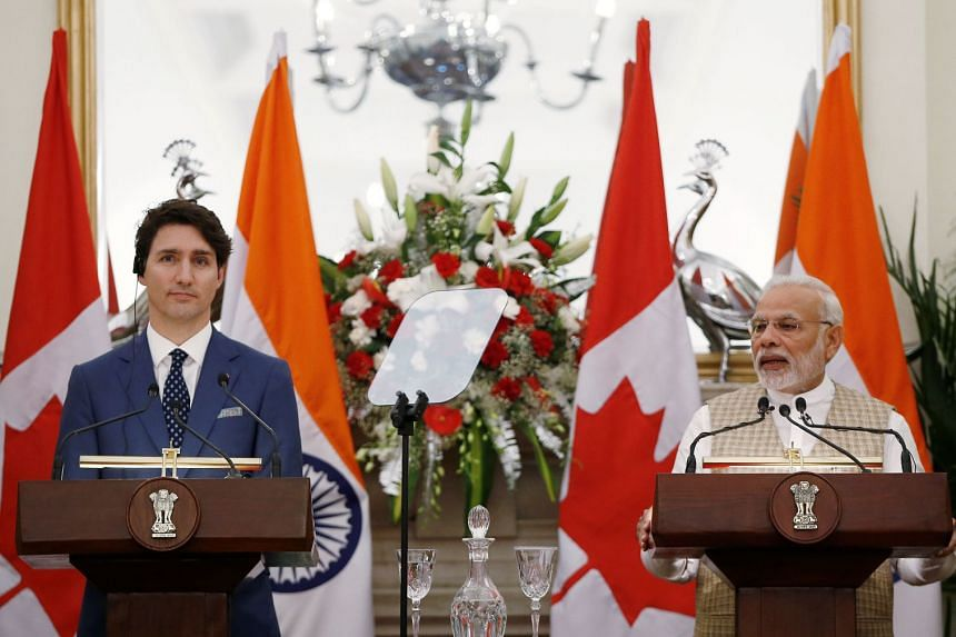 Indian Prime Minister Narendra Modi (right) reads a joint statement as his Canadian counterpart Justin Trudeau looks on, at Hyderabad House in New Delhi, on Feb 23, 2018.