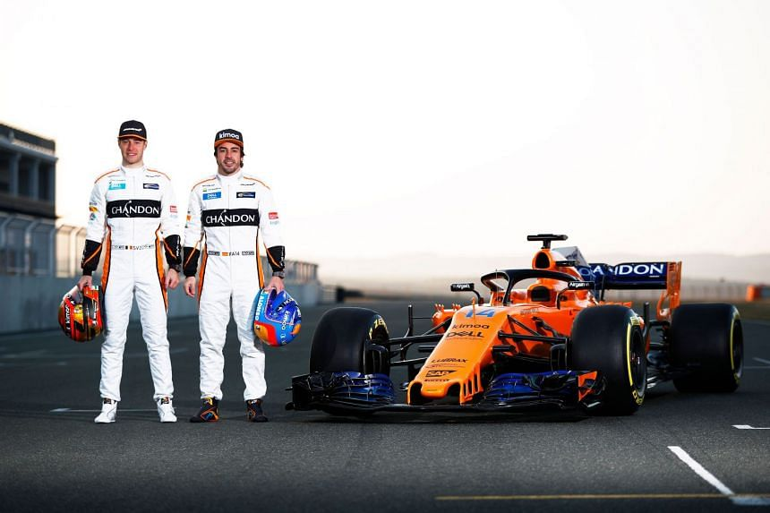 McLaren's Belgian driver Stoffel Vandoorne (left) and Spanish driver Fernando Alonso (right) posing by the MCL33 Formula One racing car for the 2018 season on Feb 23, 2018.