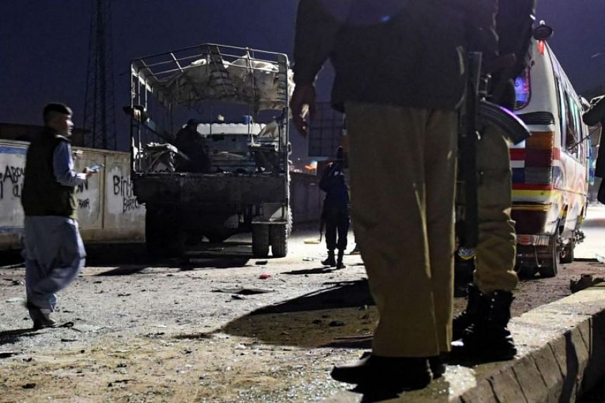 Pakistani security officials gather around a damaged police bus and truck at the site of suicide bomb attack in Quetta on Jan 9, 2018.