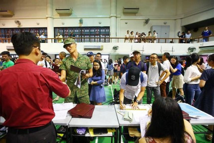 Hwa Chong Junior College students, some in their national service uniforms, lining up in the school hall to get their A-level results.