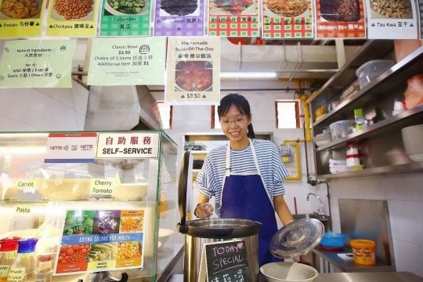 """Green Rice Bowl stallholder Ng Qin Rong at her stall in Holland Drive Market and Food Centre. Ms Ng said NEA's Incubation Stall Programme """"helped me take the leap of faith because it was a lot cheaper and less risky""""."""