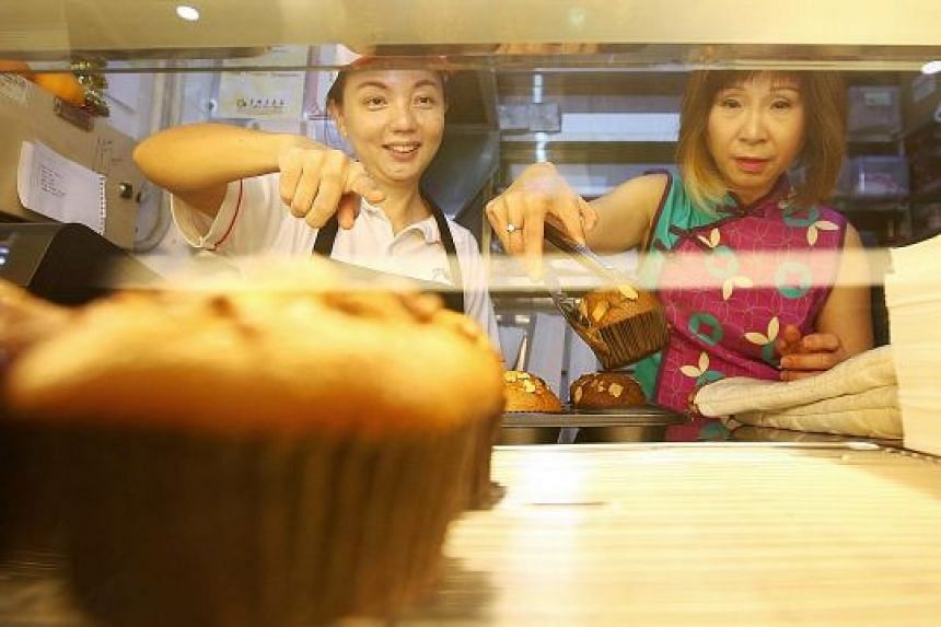 Senior Minister of State Amy Khor (right) helping Muffin Haus stallholder Tan Pey See, a former chemical engineer, display freshly baked muffins at her stall in ABC Brickworks Food Centre.