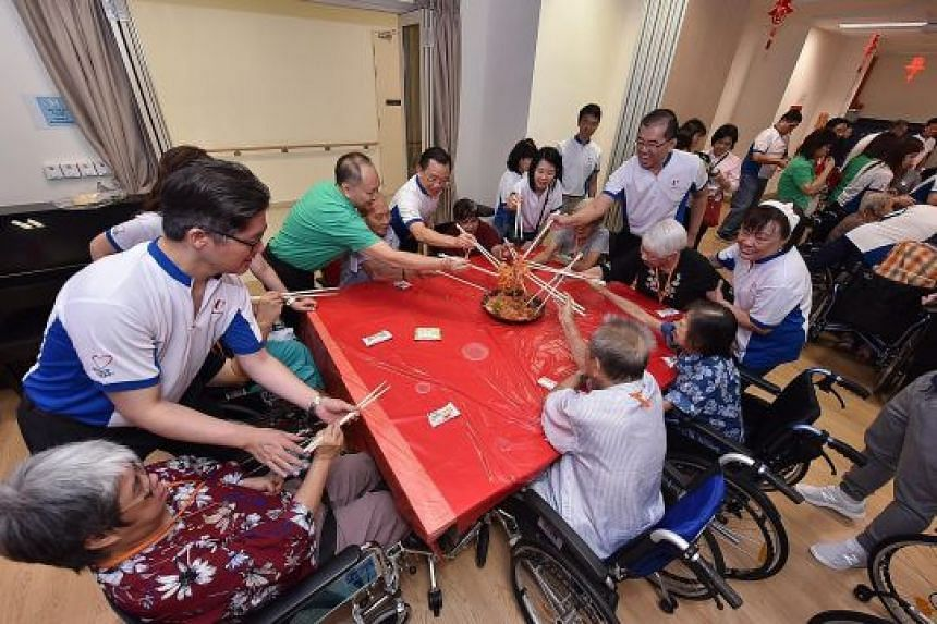 Volunteers from the FairPrice supermarket chain celebrating Chinese New Year with the elderly folk at Ren Ci @ Ang Mo Kio nursing home.