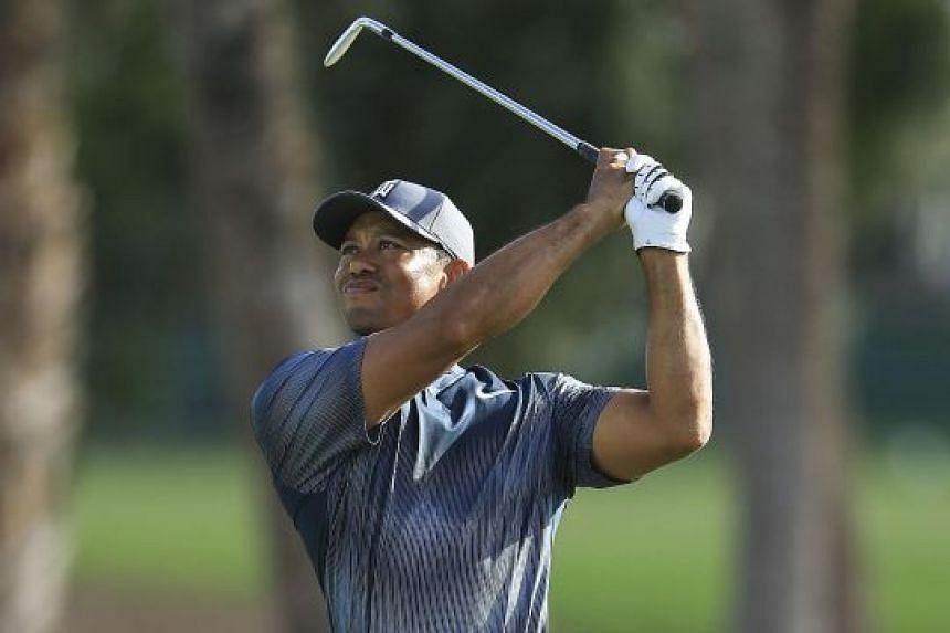 Tiger Woods playing his approach shot on the 14th hole in the first round of the Honda Classic on Thursday. He mixed three birdies with a bogey and a double bogey in difficult, blustery conditions to match his best opening round in four PGA National