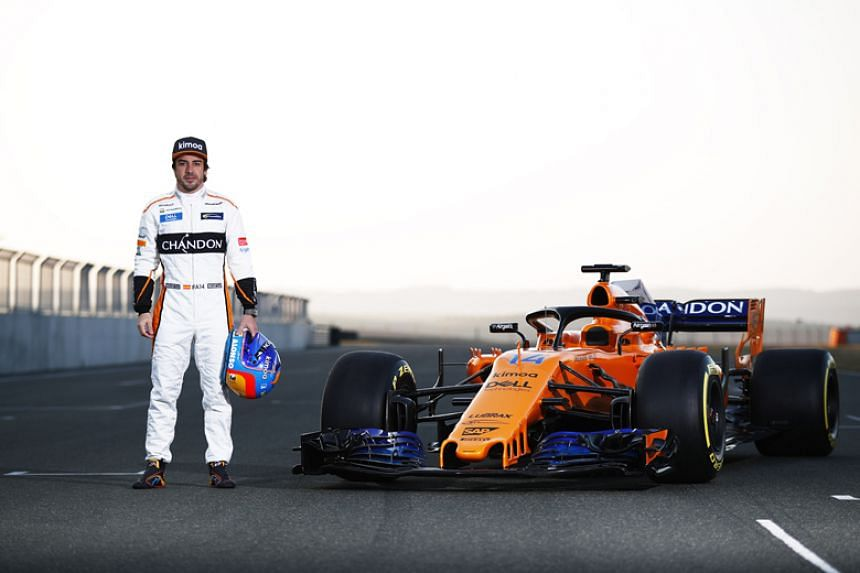 McLaren's Spanish driver Fernando Alonso poses by the MCL33 Formula One racing car for the 2018 season on Feb 23, 2018.