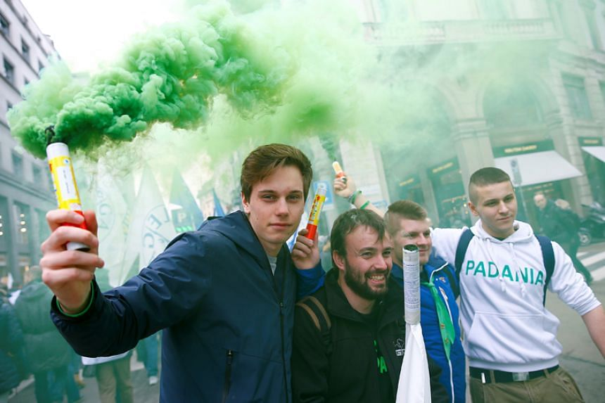 Italy's Northern League supporters hold flares as they arrive during a political rally led by leader Matteo Salvini in Milan on Feb 24, 2018.