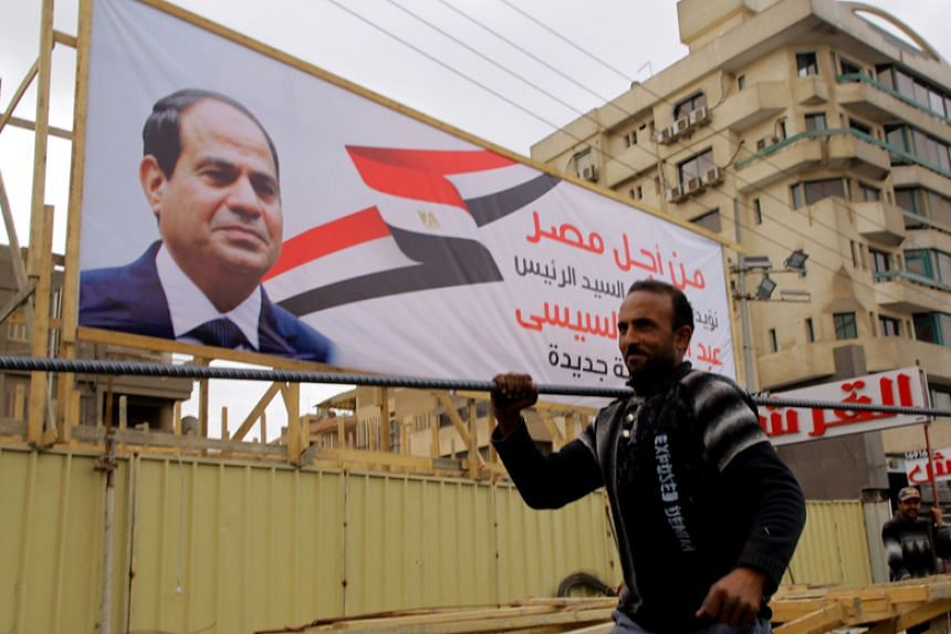 Egyptian labourers work at an under-construction site near an election campaign poster erected by supporters of Egyptian President Abdel Fattah al-Sisi, in Cairo on Feb 21, 2018.