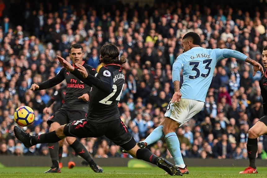 Manchester City's Brazilian striker Gabriel Jesus (right) shoots to score their third goal during the English Premier League football match between Manchester City and Arsenal, on Nov 5, 2017.