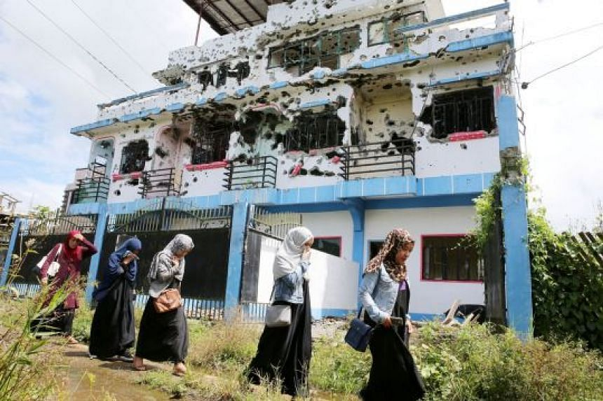 Marawi residents outside a bullet-ridden house believed to have been rented by Isnilon Hapilon and Omar Maute, the key figures in last year's siege on the city. They were killed by Philippine security forces in the last few days of the siege.