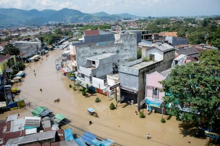 Above: Dayeuhkolot Street in Bandung was flooded yesterday after the Citarum River, the third-longest river on Java island, broke its banks.