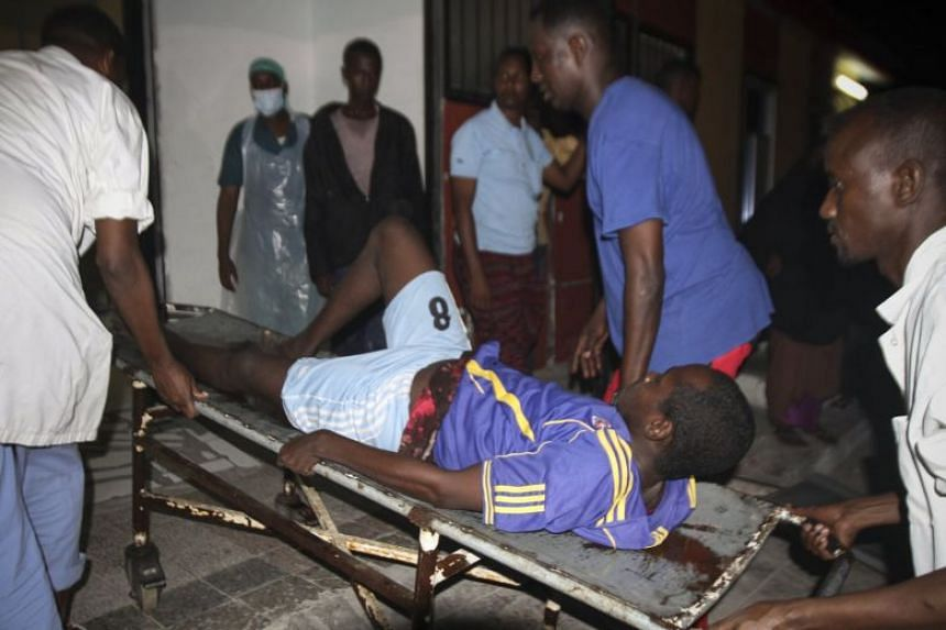 A wounded man is carried into a hospital after car bomb explosions in Mogadishu.