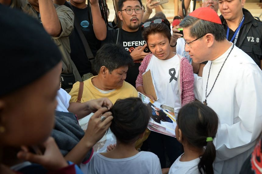 "Philippine Roman Catholic Cardinal Luis Tagle (right), archbishop of Manila, meets families of victims of extra-judicial killings during a ""march for life"" at a park in Manila, on Feb 24, 2018."