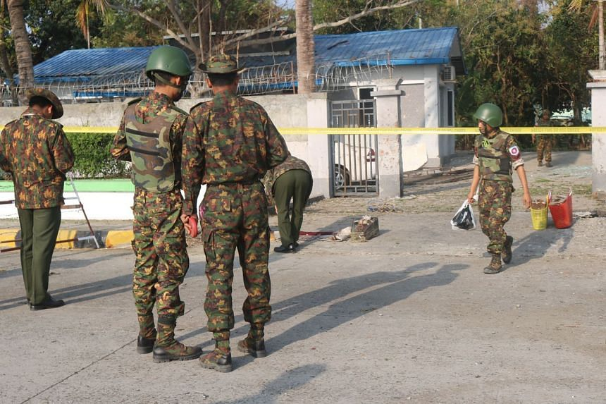 Members of the military and police stand near the site of an early morning explosion in the compound of the state government secretary's home in Sittwe, Rakhine State, on Feb 24, 2018.