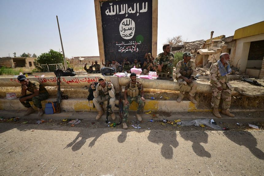Soldiers sit next to the black flag sign commonly used by ISIS militants after liberating the city of Hawija in Iraq.