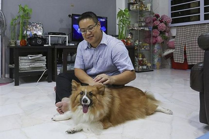 Mr Amos Koh with his dog Louie in his Bukit Batok flat. He says that after getting a fixed-rate package, the monthly instalment for his home has been reduced by $59 (from $1,567 to $1,508).