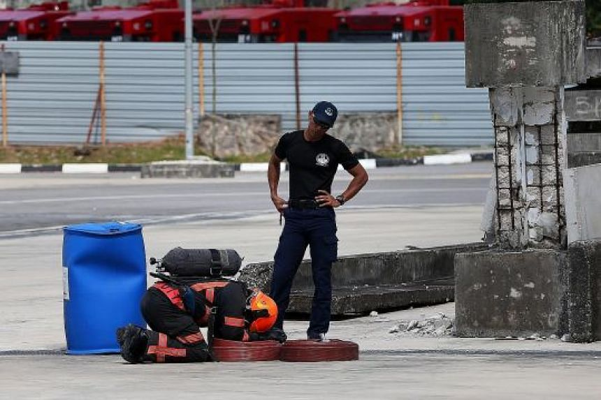 A Dart officer stands over a selection candidate who appears exhausted from having to carry two hoses, each weighing 15kg, to the endpoint of the Breathing Apparatus Endurance Circuit. The candidate also has to lug a 15kg air cylinder.