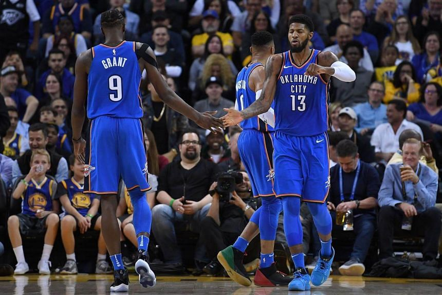 Paul George of the Oklahoma City Thunder is congratulated by Jerami Grant after he scored and was fouled against the Golden State Warriors during the second half of their NBA basketball game at Oracle Arena in Oakland, California on Feb 6, 2018.