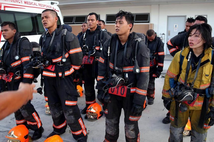 Lieutenant Gan Chea Hui (in a yellow firefighting suit), is the first female senior officer to attempt the Dart selection.